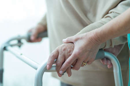 Close-up van de vrouw met behulp van rollator bijgestaan door verzorger