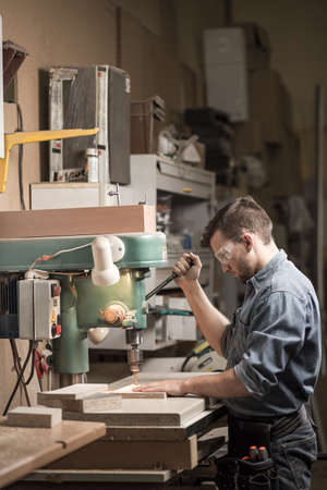 professionally: Image of carpenter labouring in professionally equiped workshop Stock Photo