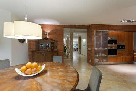 kitchen cupboard: Stylish round wooden table in contemporary kitchen