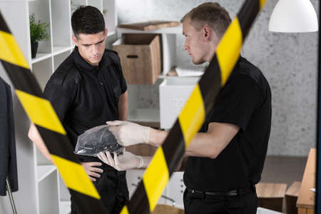 fingerprinting: Young police officer is showing secured pistol Stock Photo