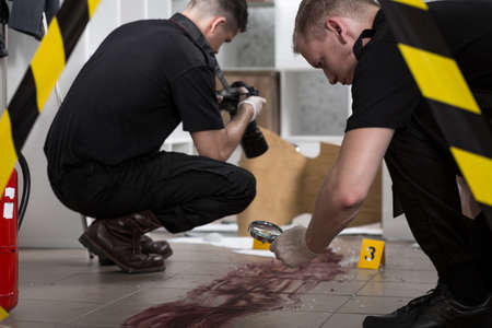 fingerprinting: Young police officer is looking at the bloody mark