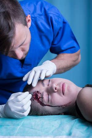 herida: Doctor joven que se viste de una herida grave en la cabeza
