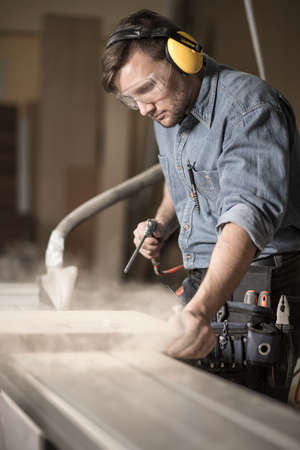 woodworker: Photo of handsome woodworker wearing muffs and protective glasses