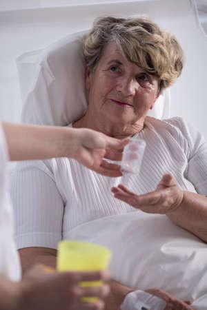 palliative: Photo of old ill woman taking medicines