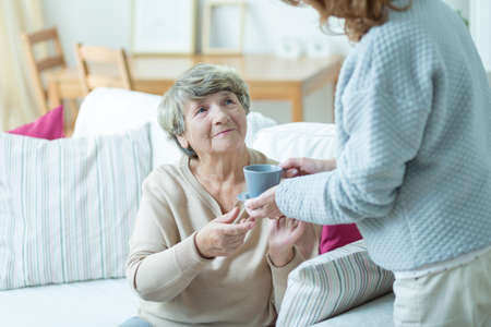 geriatric care: Caregiver giving elder woman cup of coffee Stock Photo