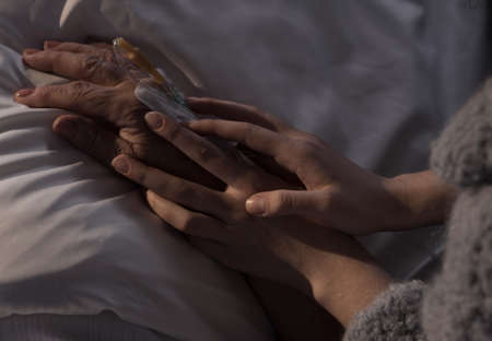palliative: Photo of woman holding terminally ill mother hand