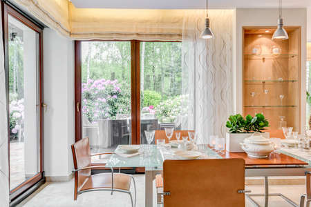 dining table and chairs: Modern style dining room with large windows