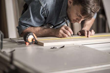 precise: Photo of precise young carpenter during work measuring board