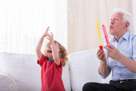 jabon: Elegante abuelo jabón dejando burbujas con el nieto Foto de archivo