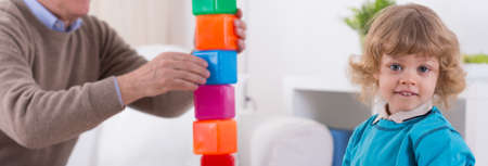 happy seniors: Cute little boy building tower of blocks with grandfather