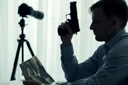 voyeur: Image of serial killer with gun waiting in room Stock Photo