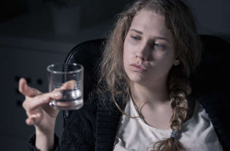 addiction drinking: Alcoholic woman is looking at the glass with vodka Stock Photo