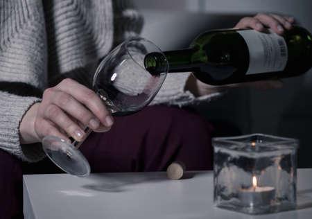 tomando vino: Mujer alcohólica está vertiendo el vino en un vaso Foto de archivo