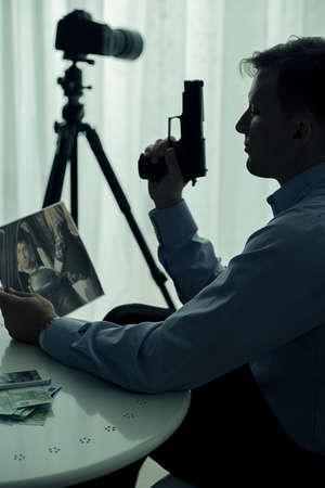 銃や犠牲者の写真と殺し屋のイメージ