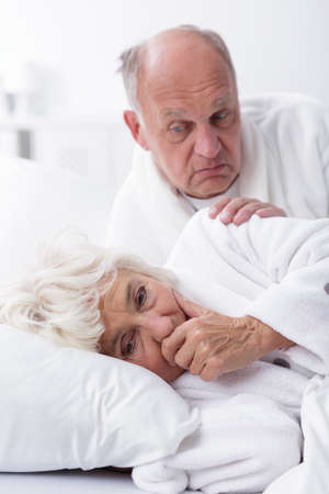 romance image: Image of sad elderly wife in bed with husband Stock Photo