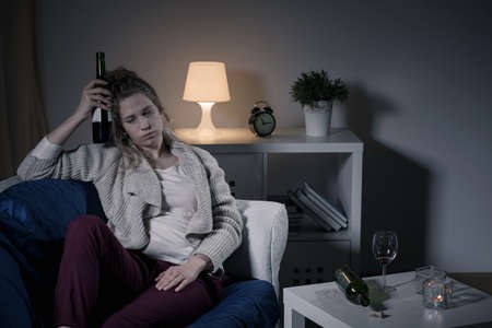 drinking drunk: Young woman is very drunk and alone Stock Photo