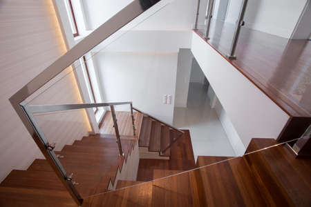 metal handrail: Modern stylish wooden and glass staircase in minimalistic design Stock Photo
