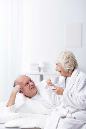 romance image: Image of elderly married couple relaxing in bed