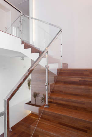 metal handrail: Modern wooden stairs with metal hand rail Stock Photo