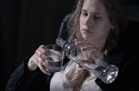 distraught: Young and sad woman is drinking vodka alone
