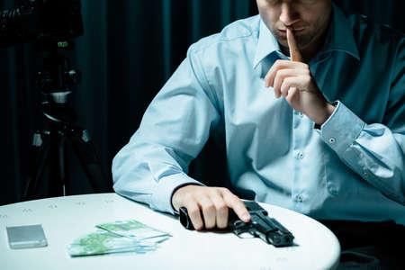銃と暗い部屋でお金で殺し屋のイメージ