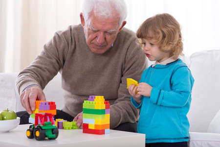 kids toys: Grandfather and his little grandson having fun together Stock Photo