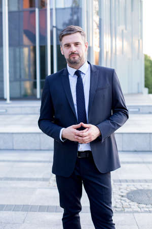 handsome guy: Businessman posing in front of business centre