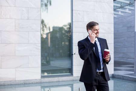 businessman suit: Businessman in black suit drinking takeaway coffee