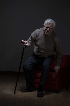 osteoporosis: Elder man trying to stand up using walking stick