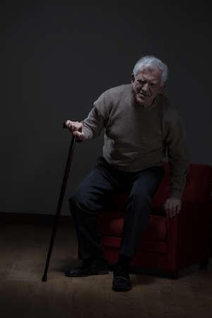 osteoporosis: Un m�s viejo hombre que intenta levantarse usando bast�n