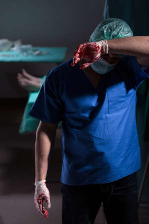 exhausted: Photo of exhausted doctor in sterile uniform after operation
