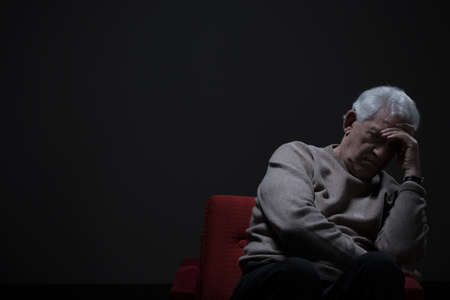 Unhappy elder man sitting alone in darkness