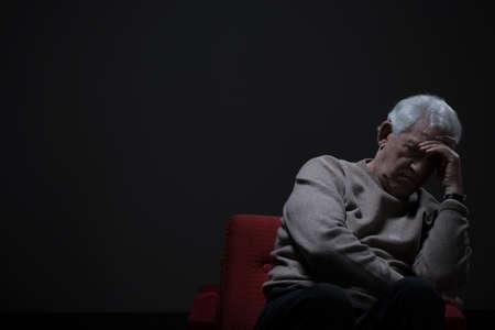 darkness: Unhappy elder man sitting alone in darkness