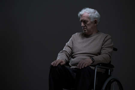 mournful: Disabled old man sitting on a wheelchair in empty room