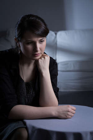 widow: Young lonely sad widow sitting alone in room Stock Photo