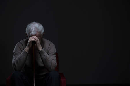 Depressed old man hiding his face behind hands Stockfoto