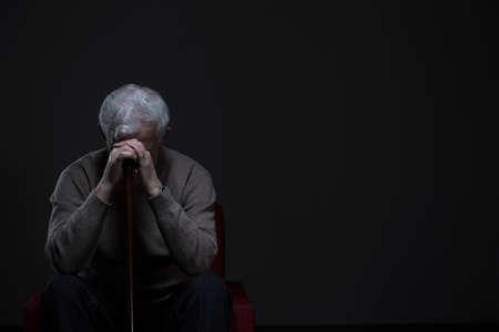 Depressed old man hiding his face behind hands Standard-Bild