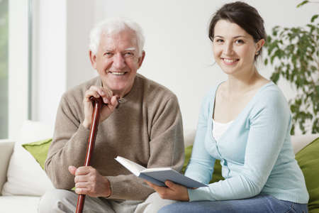 Old man holding cane and young woman reading a book