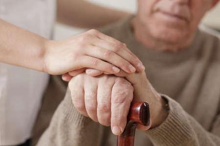 manos entrelazadas: Mujer joven y viejo hombre de la mano Foto de archivo