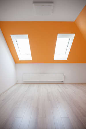 Empty attic room with orange sloped ceiling