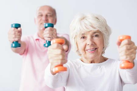 Foto van gelukkige sportieve bejaarde vrouw bij gymnastiek