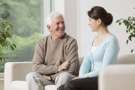 Gelukkige oude man glimlachend aan jonge vrouw
