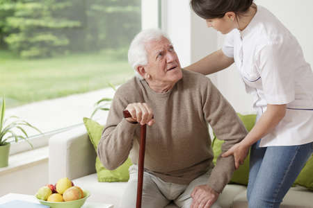 nursing assistant: Young woman helping old man to stand up