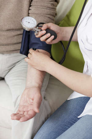 health care facility: Young woman using blood pressure monitor, vertical Stock Photo