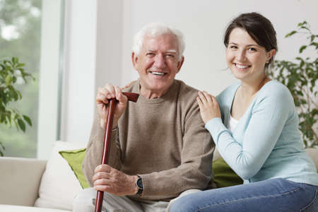 elder: Smiling old man holding a cane and smiling young woman