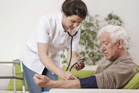 nursing assistant: Young nurse taking old mans blood pressure Stock Photo