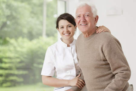 an elderly person: Young nurse taking care of old sick man