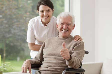 vejez feliz: Viejo hombre en silla de ruedas celebración pulgar hacia arriba