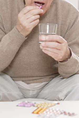 health care facility: Sick old man taking tablet with water
