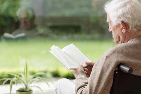 Stary człowiek na wózku inwalidzkim, czytając książkę